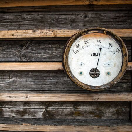 serviceable: Ancient not serviceable measuring device on wooden wall.