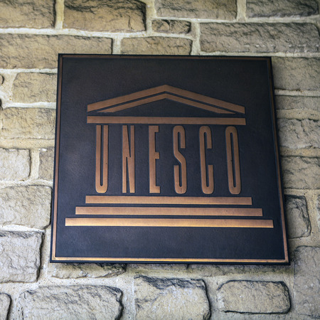 Metal emblem of UNESCO near historical heritage of Luxembourg.