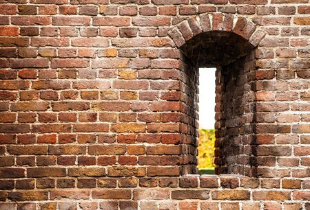 loophole: Ancient brick wall of castle with loophole as background.