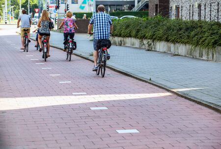 goes: Group of cyclists goes around city. Amsterdam - Netherland. Stock Photo