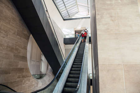 angled view: PARIS, FRANCE - AUGUST 30, 2015: Wide angled view to perspective escalators stairway. Louvre indoor. Paris, France.