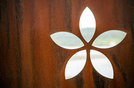 armoring: Rusty metal as background with cut-out flower form.