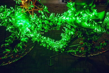 Bicycle with brightly green illumination & decorative elements at night time. Stock fotó