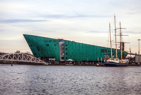 nemo: AMSTERDAM, NETHERLANDS - JANUARY 15, 2016: Nemo (Science) Museum, designed in form of  ship by architect Renzo Piano and seen from water in Amsterdam, Netherlands, on January 15, 2016.