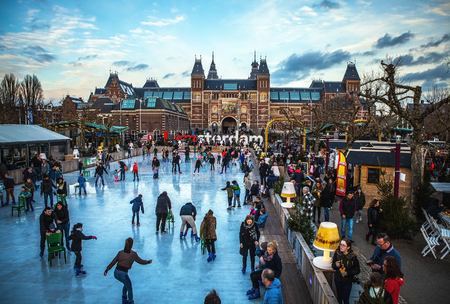 amsterdam: AMSTERDAM, THE NETHERLANDS - JANUARY 15, 2016: Many people skate on winter ice skating rink in front of the Rijksmuseum, a popular touristic destination in Amsterdam, The Netherlands.