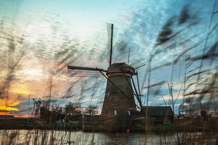 nederland: Windmills and water canal on sunset in Kinderdijk, Holland.