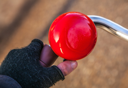 brightly: Brightly red classical bicycle bell horn.