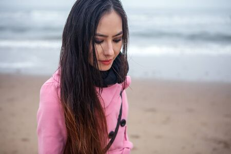 Portret van aantrekkelijke jonge vrouw met een lange mooie haren gekleed roze jas, die zich voordeed in het najaar Noordzeestrand.