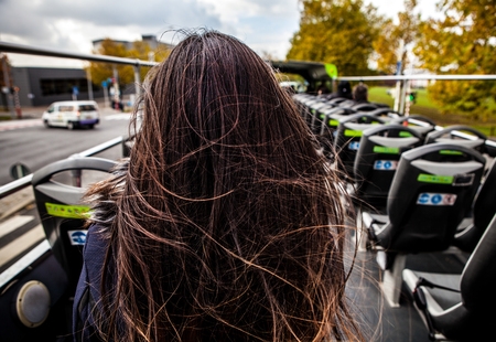 tour bus: Young woman with long beautiful hairs soaring on wind sit back in open tour bus. Stock Photo