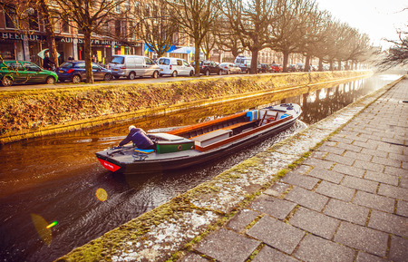 city park boat house: HAGUE, NETHERLANDS - MARCH 8, 2016: Elderly man rushes in the empty passenger boat through the narrow water channel at evening sun set on March 8, 2016 in Hague - Netherlands.