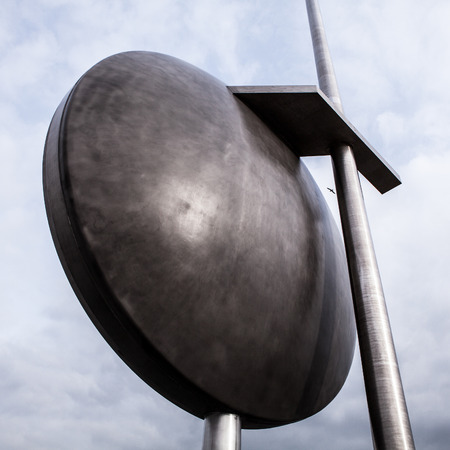 metal sculpture: Big round abstract metal sculpture against sky. Stock Photo