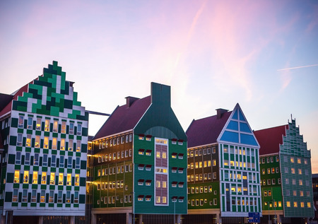 tourist attraction: ZAANDAM, NETHERLANDS - MARCH 18, 2016: Inntel hotel at twilight time. Opened in 2009, design attracts guests by incorporating traditional architecture of Zaan region on 18 March in Zaandam, Holland. Editorial
