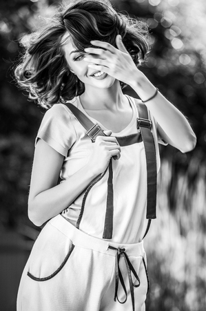 Outdoors portrait of beautiful & positive young woman in overalls which posing in solar summer garden. Black-white photo. photo