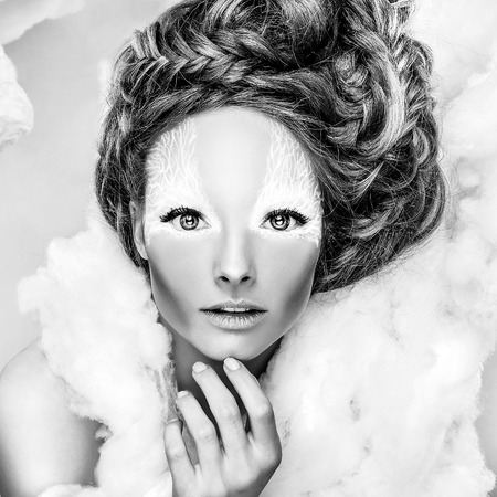 Romantic beauty with magnificent hair wandering in clouds. Fine art black-white studio fashion portrait. photo