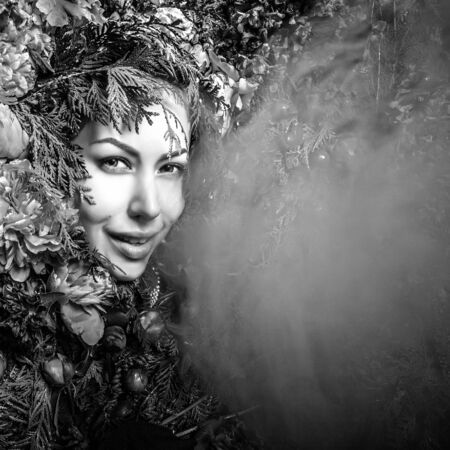Fairy tale girl portrait surrounded with natural plants and flowers.Black-white art image in fantasy stylization. photo