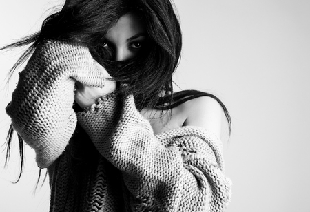Beautiful young brunette in a woolen sweater pose against studio  background. Black-white fashion Photo. photo