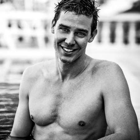 Handsome underwear man posing in swimming pool. Black-white photo. photo