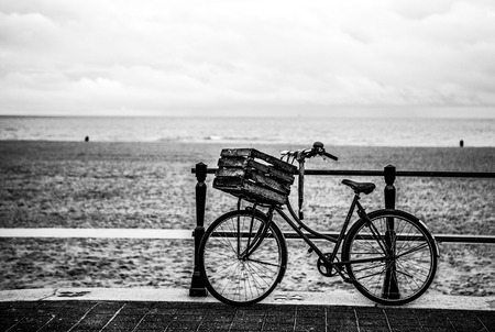 land locked: Old style bicycle with basket on coast of the North Sea in The Hague, Netherlands. Black-white photo.