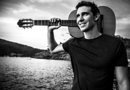 Handsome smiling guitarist. Black-white outdoor photo. photo