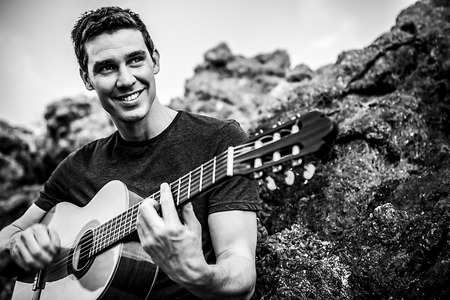 Handsome smiling guitarist play music siting on beach rock. Black-white outdoor photo. photo