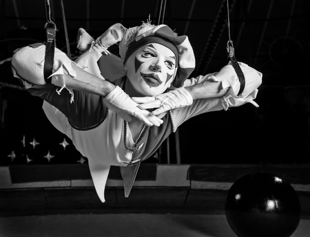 Circus air acrobat pose on ropes. Fine art black-white photo.