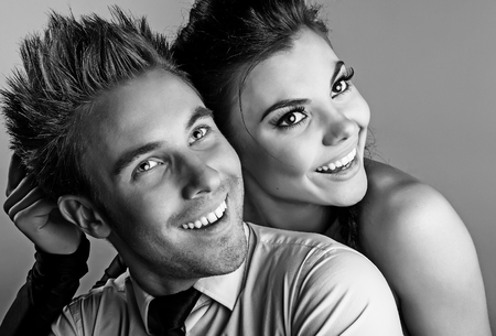 Young attractive & positive couple posing on studio background. Black-white photo. photo