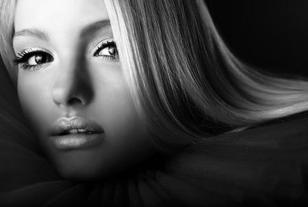 Attractive blond beauty in theatrical jabot. Black-white close-up portrait. photo