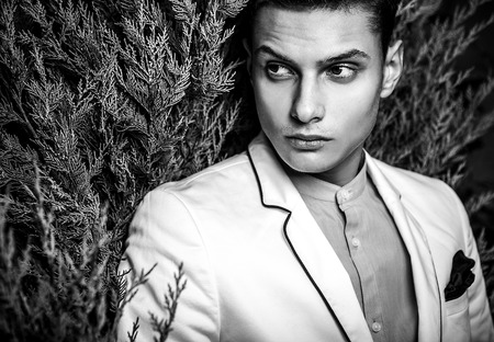 Black-white portrait of young beautiful fashionable man outdoor. photo
