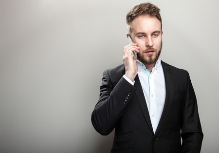 Elegant young handsome bearded man in classic black costume & white shirt. photo