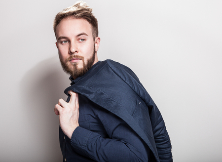 Elegant young handsome man in dark blue classic shirt and jacket on his shoulder. Studio fashion portrait. photo