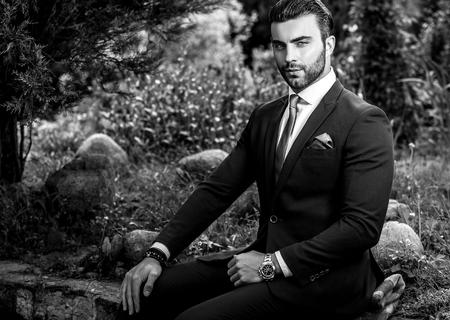 blackwhite: Elegant handsome man in classical costume pose outdoor. Black-white photo.