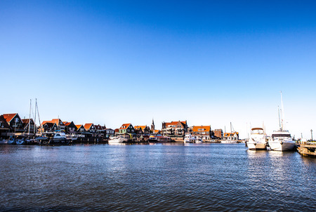 volendam: VOLENDAM, NETHERLANDS - JUNE 18, 2014: Boats and sail boats in Volendam Harbor. Volendam - a small town that has preserved the tradition of Dutch fishing villages.