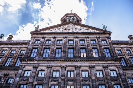 fasade: AMSTERDAM, NETHERLANDS - AUGUST 6, 2016: Famous buildings of Amsterdam city centre close-up. General landscape view of city streets and traditional Dutch architecture. Amsterdam - Netherlands.