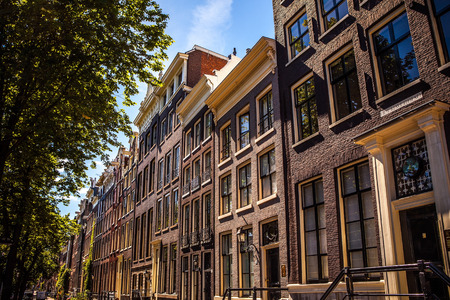 AMSTERDAM, NETHERLANDS - AUGUST 15, 2016: Famous buildings of Amsterdam city centre close-up. General landscape view of city streets and traditional Dutch architecture. Amsterdam - Netherlands.