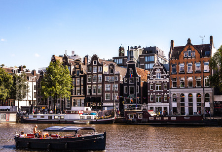 fasade: AMSTERDAM, NETHERLANDS - AUGUST 15, 2016: Famous buildings of Amsterdam city centre close-up. General landscape view of city streets and traditional Dutch architecture. Amsterdam - Netherlands. Editorial