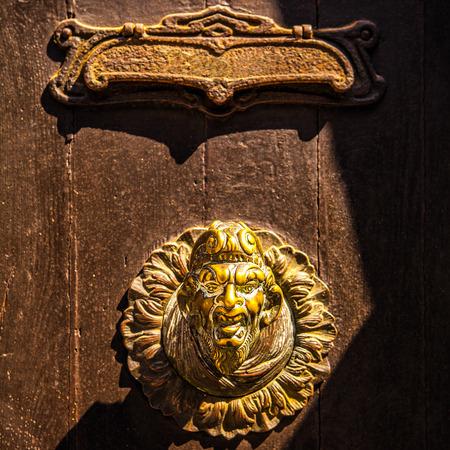 Ancient Venetian door with old door knob close-up.