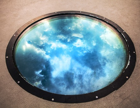 Beautiful reflection on round building window. Photo.