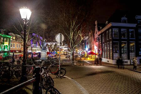 AMSTERDAM, NETHERLANDS - JANUARY 07, 2017: Night streets of Amsterdam with blurred silhouettes of passersby on January 07, 2017 in Amsterdam - Netherland.