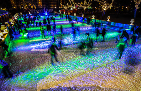 AMSTERDAM, THE NETHERLANDS - JANUARY 12, 2017: Many people skate on winter ice skating rink at night in front of the Rijksmuseum, a popular touristic destination in Amsterdam, The Netherlands. Editorial