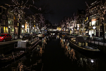 christmastime: AMSTERDAM, NETHERLANDS - JANUARY 11, 2017: Beautiful night city canals of Amsterdam. January 11, 2017 in Amsterdam - Netherland. Stock Photo