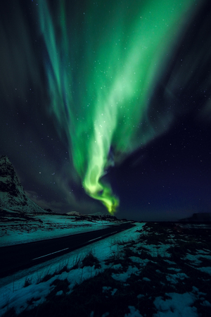 Amazing multicolored green Aurora Borealis also know as Northern Lights in the night sky over Lofoten landscape, Norway, Scandinavia. Stock Photo
