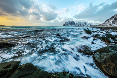 Movement of water on the shores of cold Norwegian Sea at evening time. Lofoten islands. Beautiful Norway landscape. Stock Photo