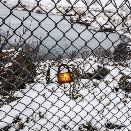 forbidden love: Rusted lock on the grid against snow background.