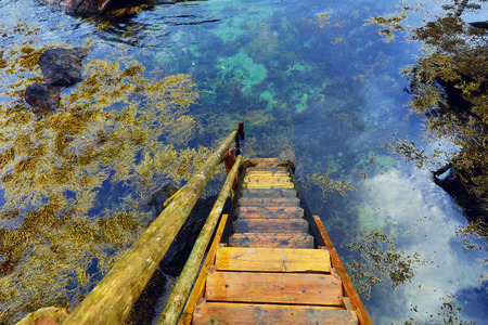 turism: Old wooden steps in the clear water of the river.