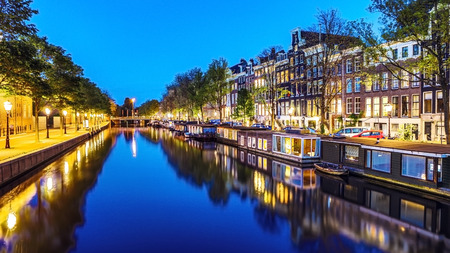 The most famous canals and embankments of Amsterdam city during sunset. General view of the cityscape and traditional Netherlands architecture. Banque d'images
