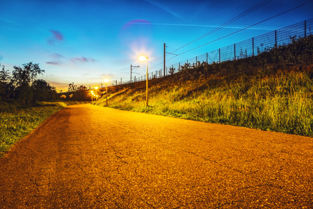 Asphalt road outside the city at twilight time.