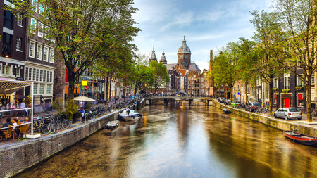 The most famous canals and embankments of Amsterdam city during sunset. General view of the cityscape and traditional Netherlands architecture. Éditoriale