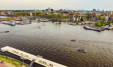 The most famous canals and embankments of Amsterdam city during sunset. General view of the cityscape and traditional Netherlands architecture. Editorial