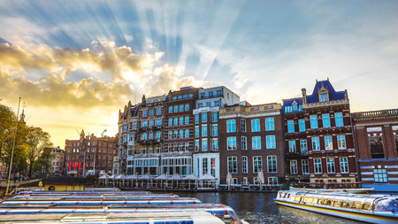 The most famous canals and embankments of Amsterdam city during sunset. General view of the cityscape and traditional Netherlands architecture. Stock Photo