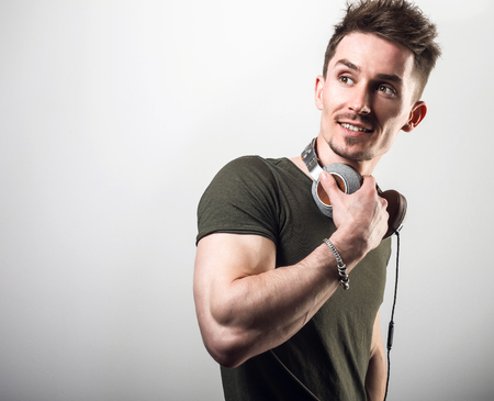 Handsome friendly sporty man in green t-shirt listening music against gray studio background. photo